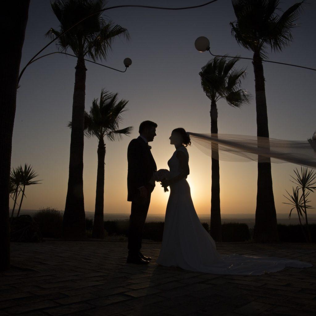 Silueta de novios en puesta de sol con palmeras